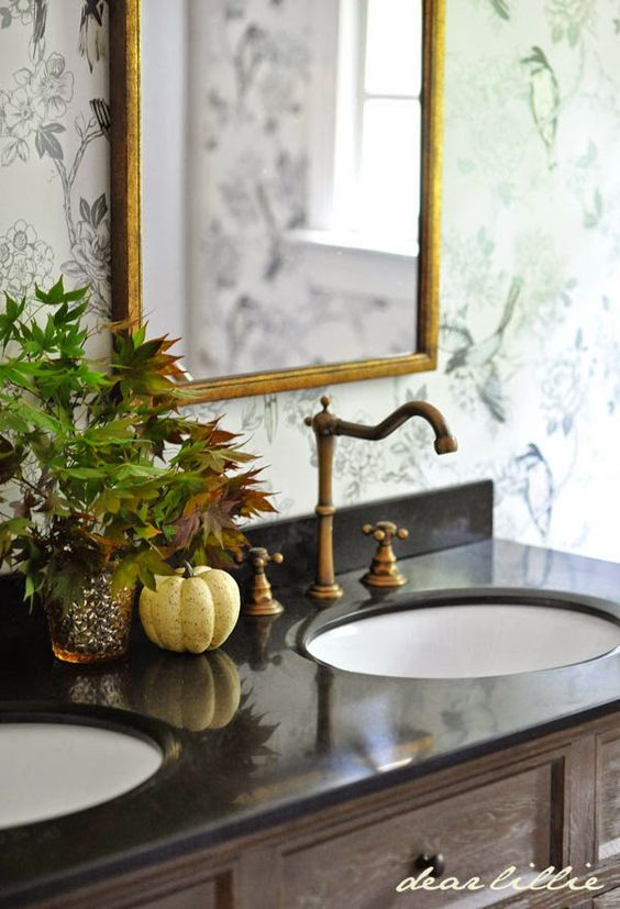 Your bathroom deserves a little fall flair too—keep it simple with a display of fall leaves and a tiny white pumpkin by the sink. See more at Dear Lillie.
