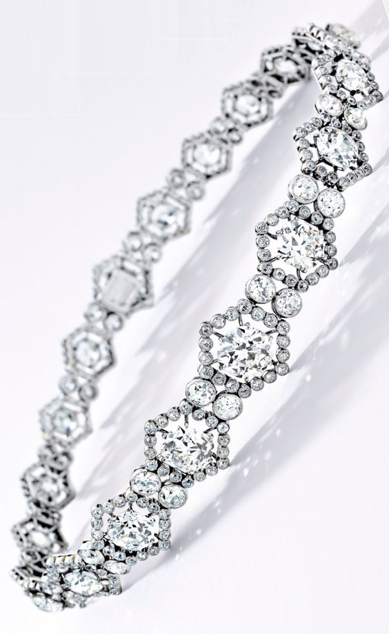 A Rare Belle Epoque Diamond Choker, Cartier, Paris, 1909. Set with 20 graduated circular-cut diamonds, each within a hexagonal millegrain diamond frame, linked by millegrain-set circular-cut diamonds, the diamonds weighing approximately 60.00 carats in total, mounted in platinum, signed Cartier Paris, choker can be divided into three sections and worn as a bracelet.