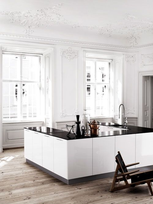 Stunning kitchen! Old, paneles walls and a rustic wooden floor in contrast to the modern and minimalistic kitchen area
