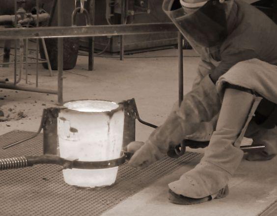 9. Der schwere, glühende Tiegel, gefüllt mit flüssiger Bronze, wird in eine Gießvorrichtung eingespannt.
