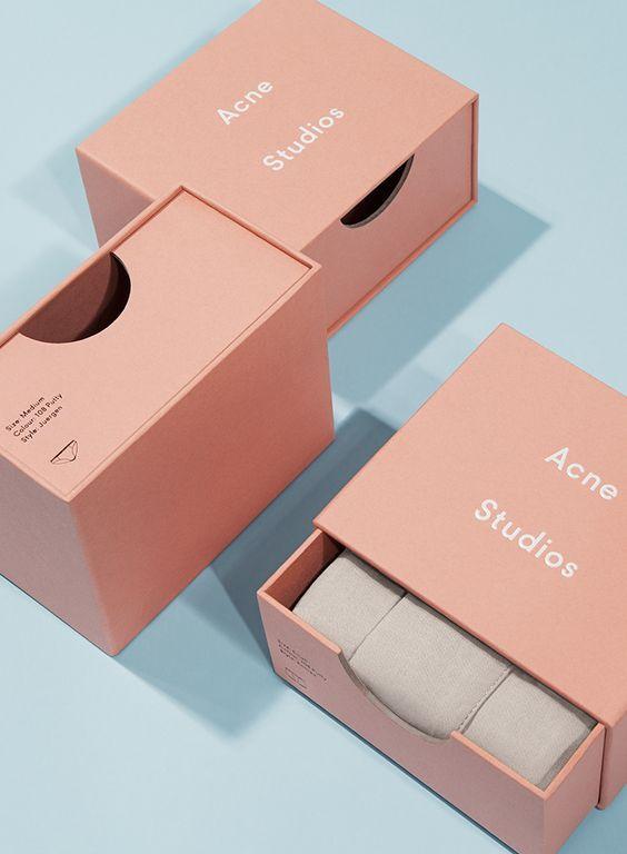 Persikan sävyinen laatikkopakkaus, jossa valkealla teksti Acne Studios