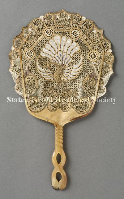 Rigid Fan 1800-1900 . Made of pierced water buffalo skin, with a painted bird resembling a peacock at the center in gold and white, and gold scrolls around the border. Made in Java.