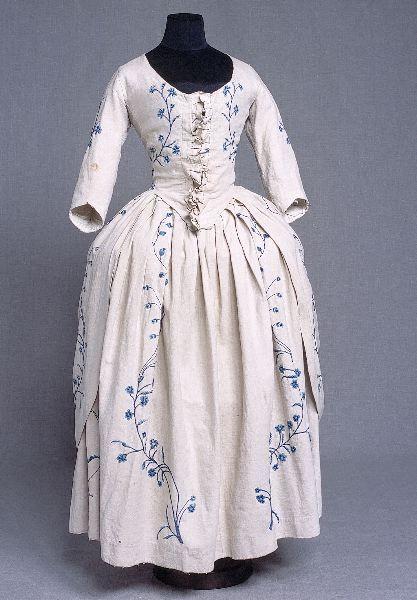 KM 67871.2   ::   klänningObjektbeskrivningBestående av robe och kjol. Beige halvlinnemed schattersömsbroderier i vitt, ljusblått och mörkblått bomullsgarn. I roben ett insytt foderliv av gråvitt linne, vilket snöras samman framtill. Kjolen har runt omkring i nederkanten en skoning av kyprat linne, ungefär 5 cm bred. Halvlång isydd ärm, fodrad med vitt linne. Roben har framtill en veckad garneringsremsa av tyget. 2 st klädda knappar baktill, omkring 10 cm nedanför midjan.