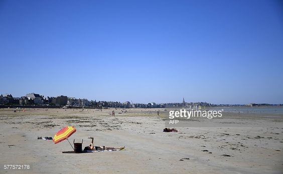 A woman lays on a beach of Saint-Malo, western France,... #saintlyphard: A woman lays on a beach of Saint-Malo, western… #saintlyphard