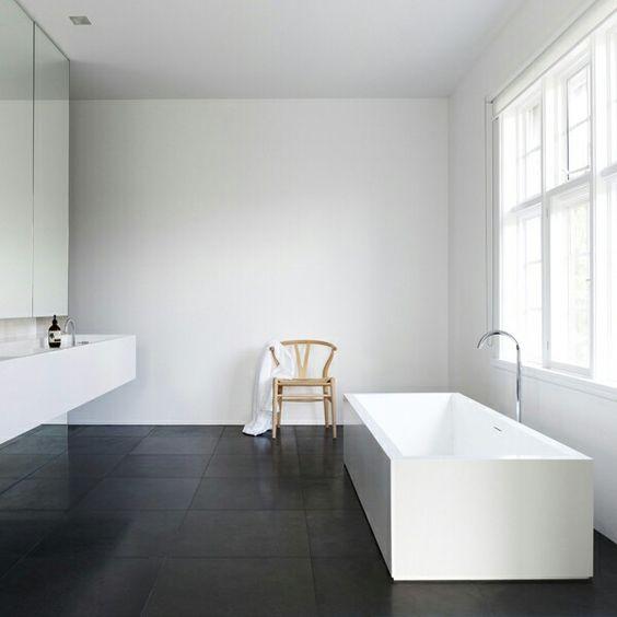 baño minimalista, con paredes, encimera y bañera exenta blanca, y suelo color carbón