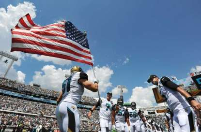 Jacksonville Jaguars middle linebacker Paul Posluszny (51) carries the flag onto…