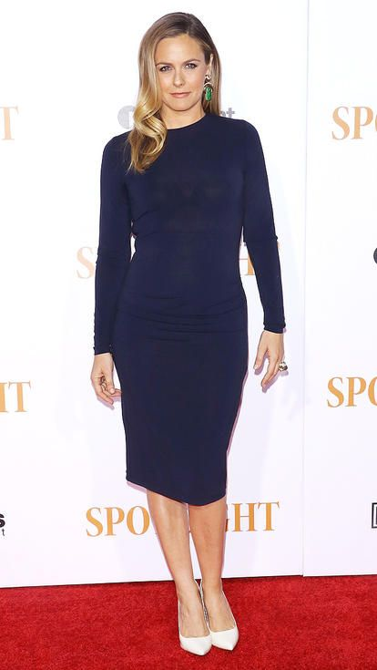Alicia Silverstone in a long-sleeve navy dress and white heels
