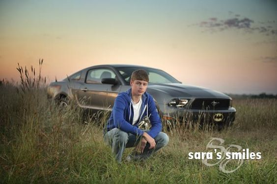 Senior boy poses with his mustang car on outdoor session on location during summer morning in a wheat field