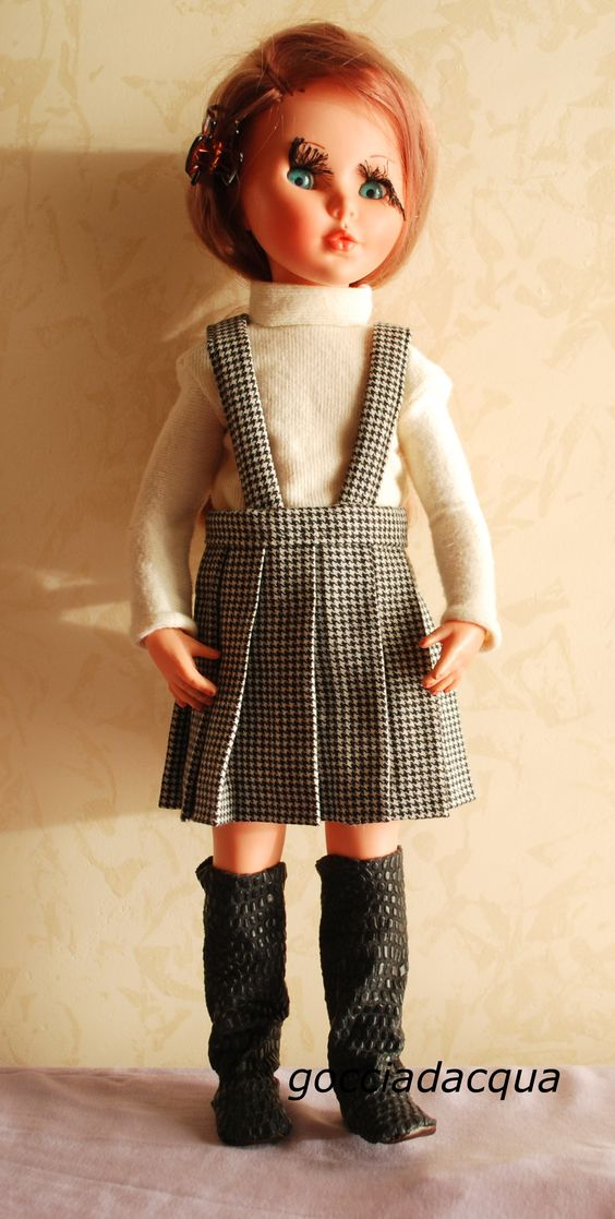 Sheila in alti stivali neri abbinati a repro della gonna 'Twist' e maglione bianco ispirato a 'Tonale'.