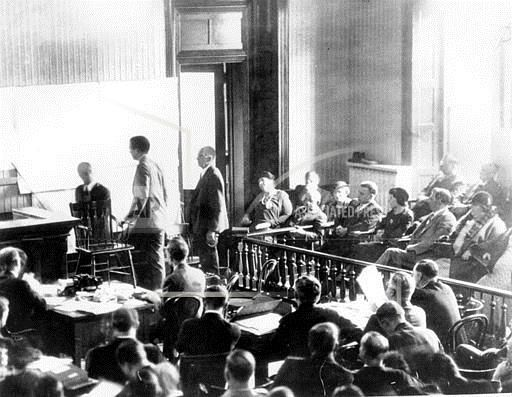 Col. Charles A. Lindbergh, standing center, identifies an architect's map of his home in Hopewell, N.J., which shows the room from which Bruno Richard Hauptmann is accused of having kidnapped the aviator's young son nearly three years ago. Lindbergh took the stand during the kidnap trial of Hauptmann at the courthouse in Flemington, N.J., on Jan. 3, 1935. (AP Photo)