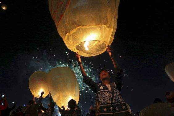 People light traditional home-made paper lanterns during the annual Tazaungdaing ballon festival in Taunggyi