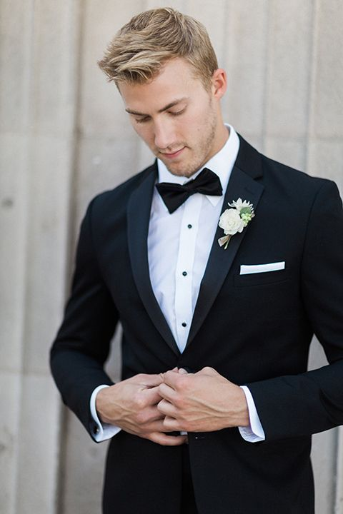 Boutonniere Style Black Notch Lapel Tuxedo With A Black Bow Tie And A Simple White Floral Bouto Wedding Suits Men Black Groomsmen Attire Black Groom Suit Black