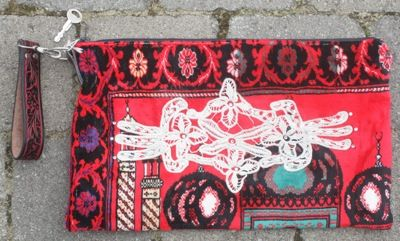 red muslin prayer rug turned in to awesome clutch with doily appliqued and tooled leather belt strap.
