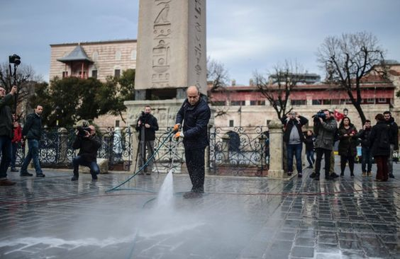 Workers clean up at the site of the attack in Istanbul's Sultanahmet tourist...