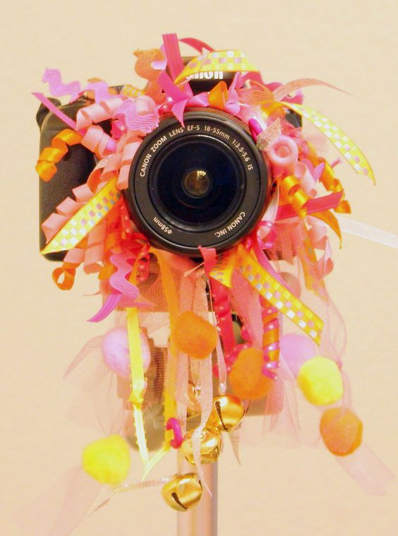 """Cute and """"noisy"""" Baby Photography Camera Lens Bling! Has ALL KINDS of BRIGHT colors, FLUFFY ribbons, and JINGLE BELLS to get your subjects attention! $14. (free shipping) fits most lenses. Frick@FrickPhoto.com"""