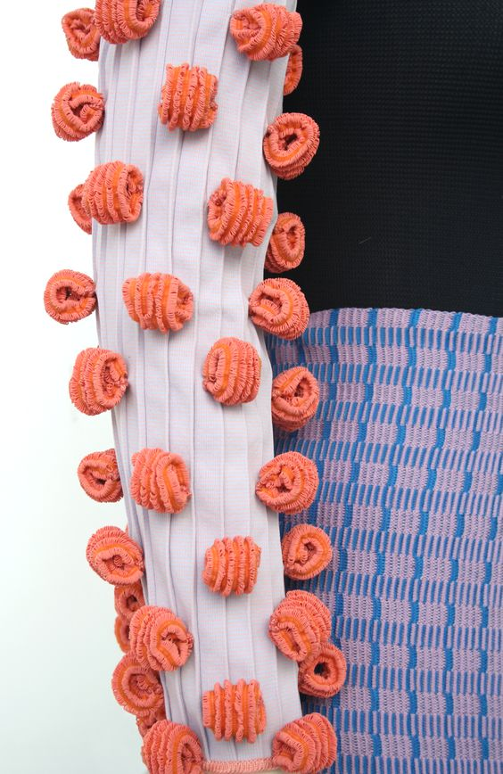 The inspiration behind Karoline's collection comes from her fascination with the sea, in particular corals. She wanted to study the free-flowing shapes, textures and vibrant colours and capture the qualities in a variety of methods and mediums. The technical aspect of re-creating these forms through a knitted medium found numerous challenges. From primary research Karoline transformed ordinary materials into complex and unexpected knitted pieces by combining yarns such as elastic and…
