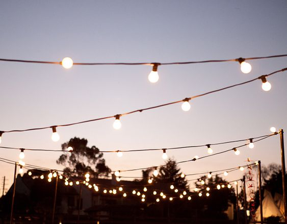 Feast in the field is one of The Style Co's signature outdoor weddings, featuring festoon lighting, a winding dining table and a custom built outdoor cinema and lounges