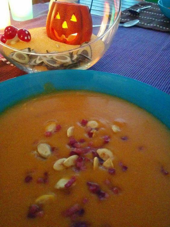 Kürbissuppe garniert mit gebratenem Speck und Kürbiskernen.