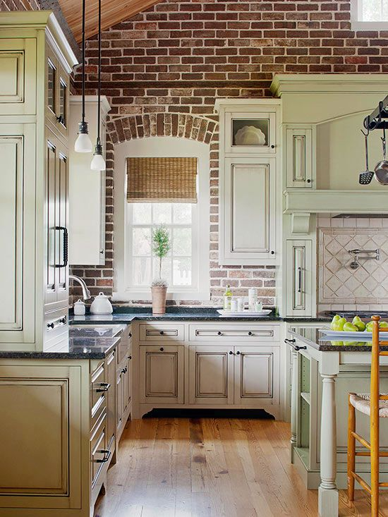 This new kitchen features a brick wall with an old-world look and feel. The rustic look of natural brick adds texture to any room. White cabinets add contrast while blending beautifully with the light-color grout.