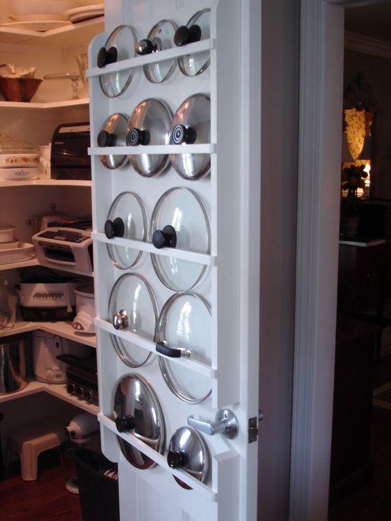 utilice las barras de cortina en la parte posterior de la puerta de la despensa de organizar tapas de ollas... o usted puede construir su propio organizador de la madera como se muestra aquí.