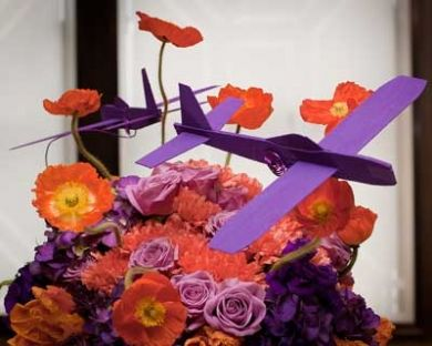 A lighthearted floral arrangement--complete with airplane. The bride requested her favorite color palette--tangerine and purple.