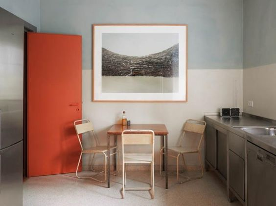 """In this small dining space, both the horizontal and the vertical are emphasized by the horizontal color band that divides the space in half. Tip: The large photo above the table acts as a window drawing your eye into the """"view"""" beyond. 