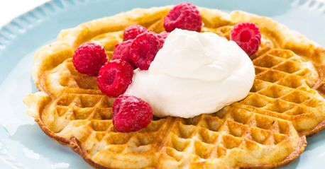 Waffles with whipped cream and raspberries. Yes, you can gave them for breakfast.