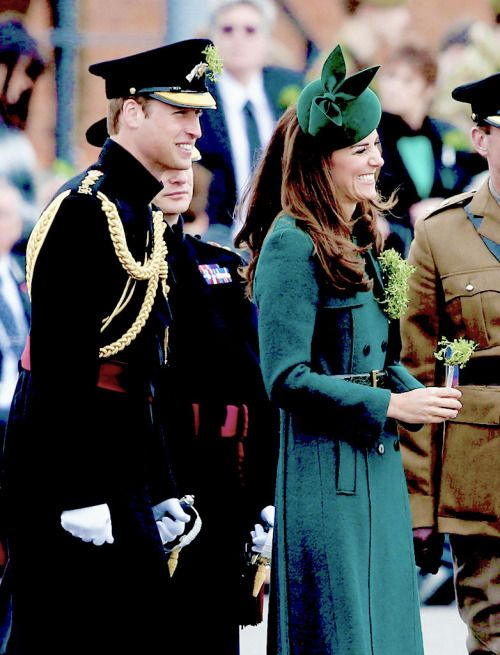 The Duke and Duchess of Cambridge laugh as they present 'Shamrocks' during the St Patrick's Day parade at Mons Barracks on March 17, 2014.