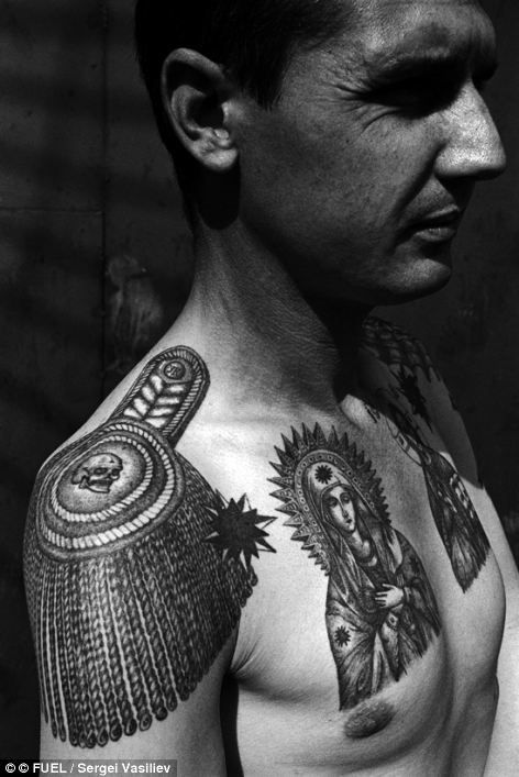 The epaulette tattooed on the shoulder, the thieves' stars and religious tattoos on the chest all denote this thief's high rank. The skull in the centre of the epaulette can be deciphered as: 'I am not and will never be a slave, no one can force me to work'. 'YK' indicates the bearer has been through the 'Intensive Colony'