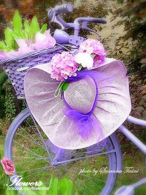 Flowers in the basket of a bike with a large lavender hat with flowers on the handlebars