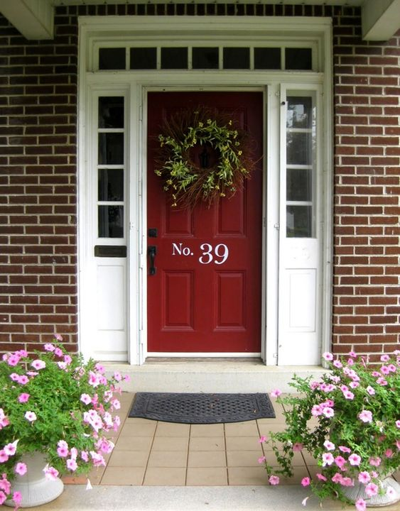 This charming front porch has a door mat, perennials potted in white urns, and the house number boldly placed on the center of the door in a contrasting white.: