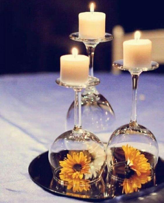 Tischdeko mit Kerzen und Blumen unter Glas: