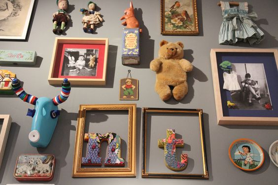 This gallery collection of antique looking toys and frames is hung on a wall in the perfect shade of grey.