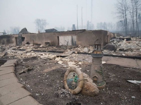 FORT MCMURRAY, AB - MAY 07: Home foundations and skeletons of possesions are all that remain in parts of a residential neighborhood destroyed by a wildfire on May 7, 2016 in Fort McMurray, Canada. Wildfires, which are still burning out of control, have forced the evacuation of more than 80,000 residents from the town.