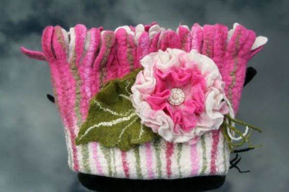 Wet felted clutch with floral adornment.
