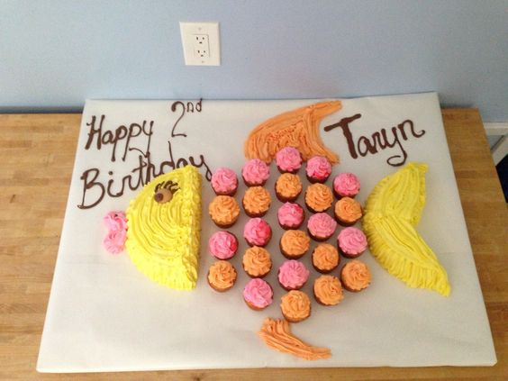 "Fish cupcake cake. I double a similar idea so this is 24 cupcakes and a 9"" round cake."