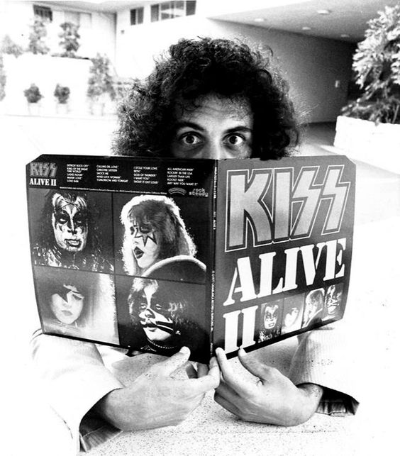 Gene Simmons of Kiss playing peekaboo behind a copy of their legendary live album Alive II, 1978.