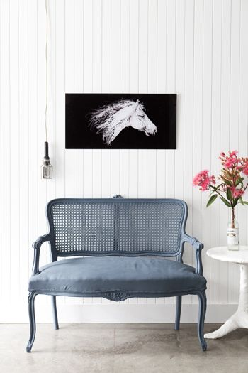 the grey double chair is so gorgeous against the white panelling :