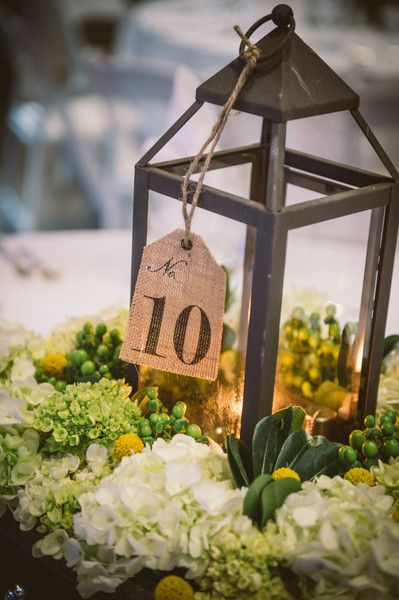 Love these wedding centerpieces featuring iron lanterns wrapped with hydrangea and craspedia wreaths! {Documentary Associates}
