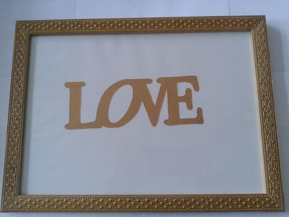 Quadro com recorte da letra em papel dourado.