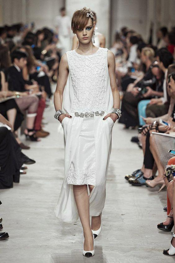 Vestido con varias capas estructuradas y superpuestas con texturas tridimensionales y broches-joya en la cintura, de Chanel.