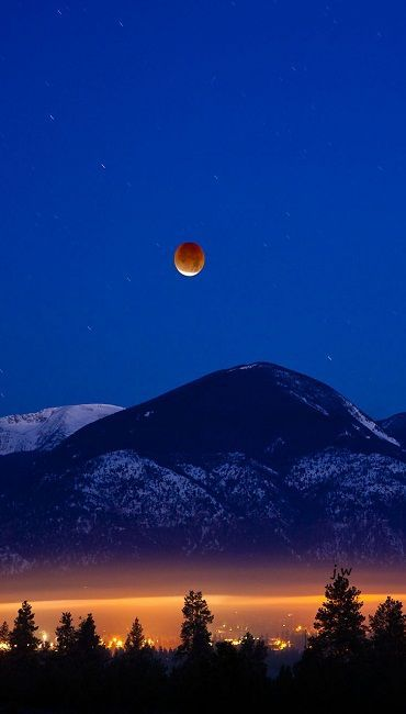 Total lunar eclipse at dawn above Lolo Peak and the Bitterroot Mountains in Florence, Montana, USA