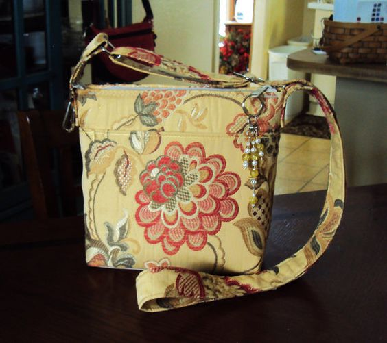 """Etsy (SewIngeniousDesigns) Bright spring bag in woven textile w/ uniquely smooth texture & bright red floral centerpiece. 8"""" W x 8.5"""" T w/ roomy interior on a 4"""" protective nylon base. Fabric handle adjusts to 24"""" drop from the shoulder & a convenient key fob is attached. Purse front has a 7"""" W x 6"""" D magnet snap closure pocket for cell phone & more. Bright yellow gold interior has 2 drop pockets &  7"""" zipper pocket. Full-width zipper has sparkly wire beaded tassel. All nickel chrome…"""