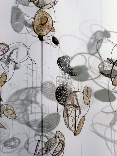 wire & paper sculpture create art with shadows on the wall behind.