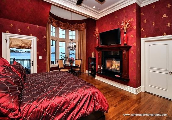 Rich and opulent, romantic, ornate master bedrooms with various layers of deep red hues with, red walls, bedding, rugs, seats, curtains and more in Traditional, Art Deco and Contemporary styles. Rich velvet canopy, luxe satin bedding and a deep red color palette. The beveled paneled walls are painted in Sherwin Williams Lanyard. Photo credit: Dennis…