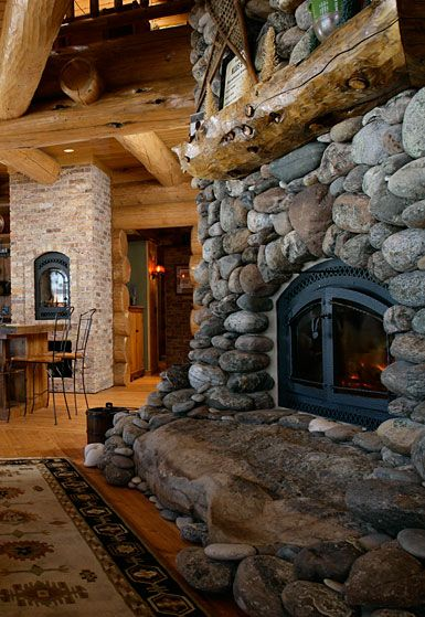 native river rock for a fireplace design in the vacation log home