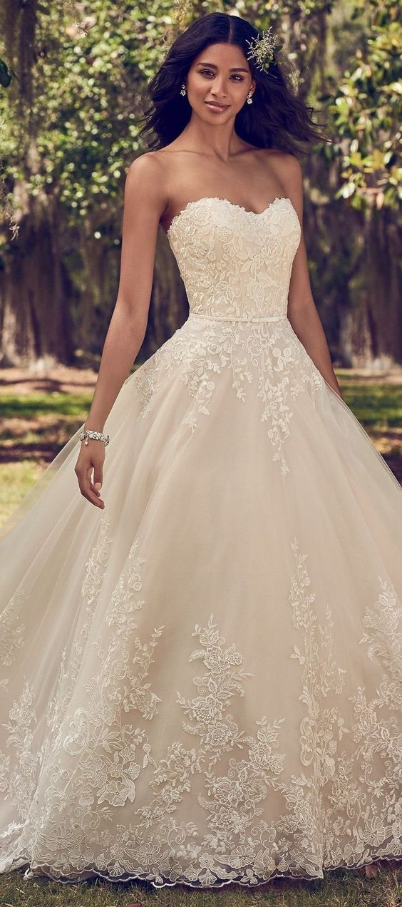 Maggie Sottero - VIOLA, Lace motifs cascade over tulle in this ballgown wedding dress, featuring a strapless scoop neckline and belt with bow detail. #laceweddingdress #ballgown #ballgownweddingdress