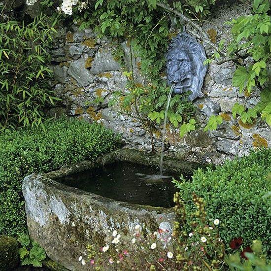 Rustikales Wasserspiel. Eine alte Steintrog, mit einem Löwen-förmigen Auslauf, dreht sich eine rustikale Gartenmauer in eine ungewöhnliche Wasserspiel. Box, Erigeron und Bambus Rand der Fläche, die ihm einen magischen Auftritt.