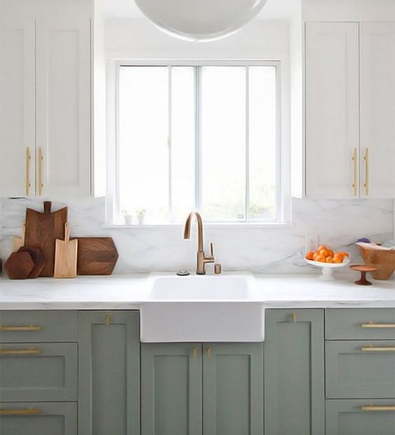 All eyes on this picture-perfect, whitewashed setting complete with a marble backsplash, sleek brass pulls, and an equally stunning shade of gray.