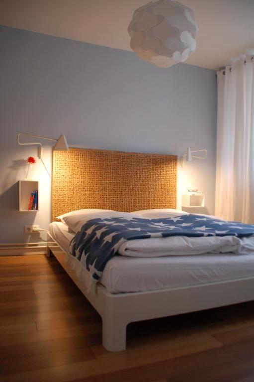 Gemütliches Schlafzimmer mit großem Bett vor hellblauer Wand in